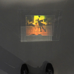 Image of art hologram Down from the Peak by Martina Mrongovius the hologram shows a shadow and reflection of the photographer and has been photographed so that you can see the photographers feet