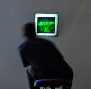 Martina Mrongovius 'We're all looking' Beyond the Window, Bus Gallery Melbourne (2008) | image shows a seated viewer leaning to play the animation of a greenish reflection hologram in metal frame