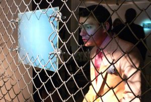 Person looking at hologram by Martina Mrongovius attached to fence